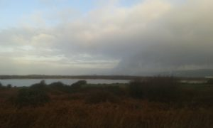 This is a picture of Kenfig Pool looking towards the steelworks at Margam